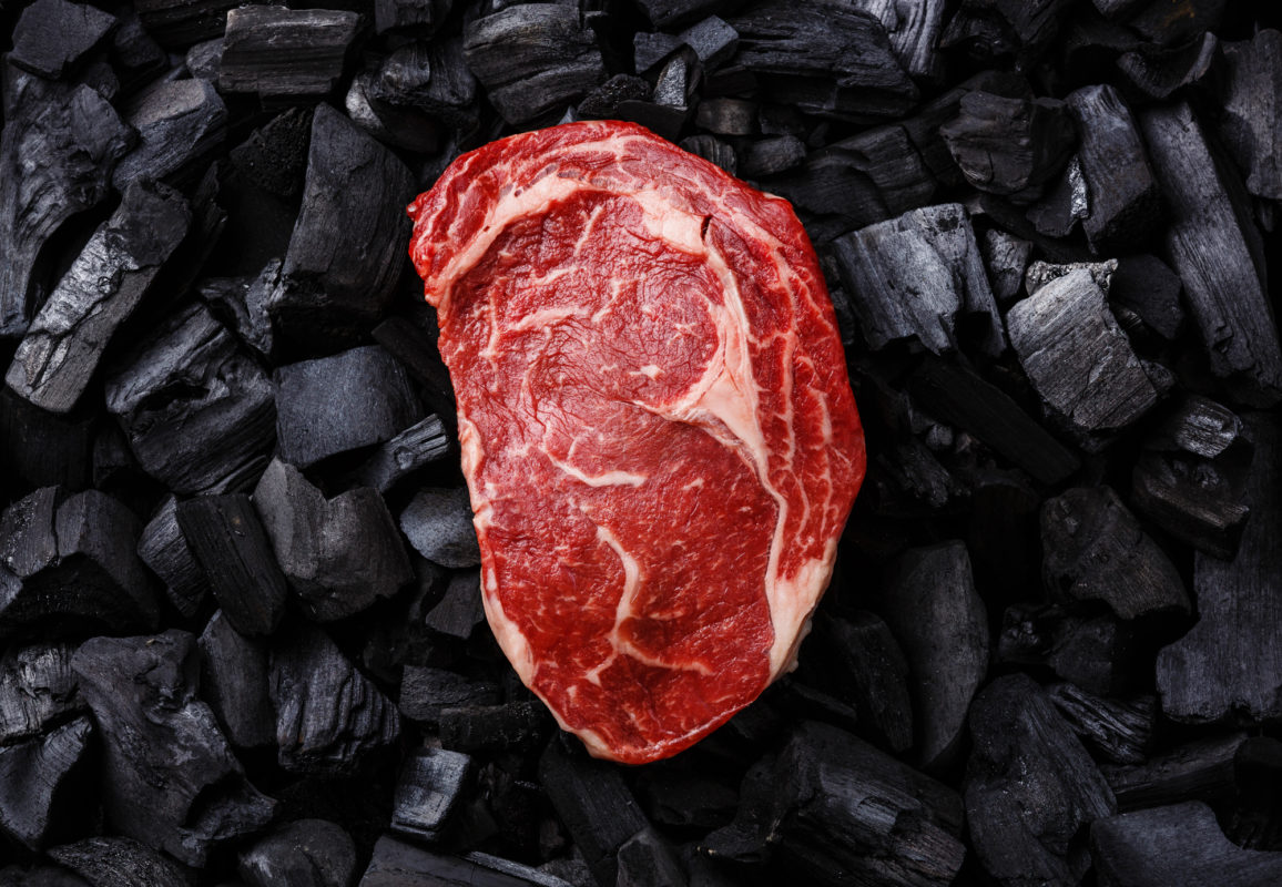 Raw fresh meat Ribeye steak on black charcoal background